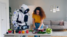 White robot and woman cook dinner together. Cyborg and human concept. White robot and woman cook dinner together. 4K stock footage