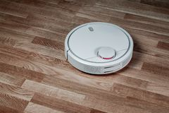 White robotic vacuum cleaner runs on laminate floor. Robot controlled by voice commands for direct cleaning. Modern smart royalty free stock photography