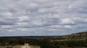 White rock road in the mountains. Below a cloudy sky stock image