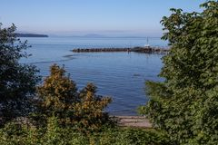White Rock`s pier and breakwater, Semiahmoo Bay, San Juan Islands. Looking down to White Rock`s beach at high tide with it`s pier and breakwater in the middle Stock Photography