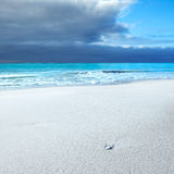 White rock in a white beach under blue cloudy sky. Ocean seascape. White rock or pebble in a white sandy beach under blue cloudy sky in a bad weather. Waves on Royalty Free Stock Photos