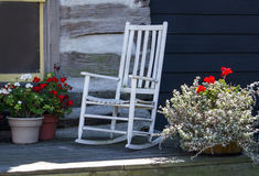 White rocker by log cabin Stock Images