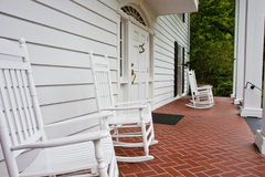 White Rockers on Red Tile Porch Royalty Free Stock Photos