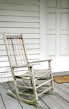 Antique White Rocking Chair on Porch. Old white rocking chair on wooden porch Royalty Free Stock Photos