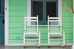 White Rocking Chairs on New Orleans Porch. Two white rocking chairs on porch of green New Orleans American Home stock images