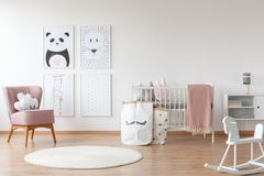 Pink armchair in child`s room. White rocking horse and carpet in child`s room with pink armchair, paper bags, drawings and bed Stock Photos