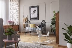 White rocking horse in grey child`s bedroom interior with poster above bed. Real photo stock images