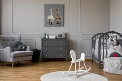 White rocking horse on rug in grey kid`s bedroom interior with poster above cabinet. Real photo. Concept royalty free stock photography