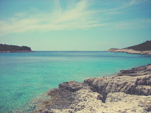 White rocky beach and clear blue sea on a sunny summer day; faded, retro style Royalty Free Stock Images
