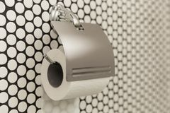A white roll of soft toilet paper neatly hanging on a modern chrome holder on a light bathroom wall. Close up. A white roll of soft toilet paper neatly hanging Stock Photos