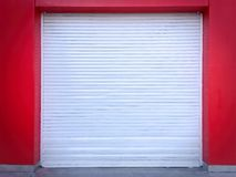 White Roll-up Door on Red Wall of the Garage Stock Image