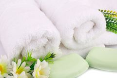 Towel, soaps and flowers. White rolled towels with soaps and flowers closeup picture Royalty Free Stock Images