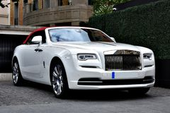 White Rolls Royce Luxury Car. Rolls-Royce Holdings plc is a British multinational public limited company incorporated in February 2011 that owns Rolls-Royce, a Stock Photos