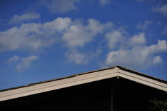 White roof in front of blue sky and cloud background Stock Images