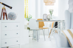 White room with dresser. Communal table and chairs stock photo