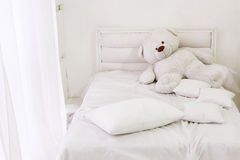 White room interior with bed, window, pillows and bear stock photography