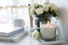 White room interior decor with burning hand-made candle and bouq. Uet of fresh roses on table, luxury home decorations in daylight closeup Royalty Free Stock Photo