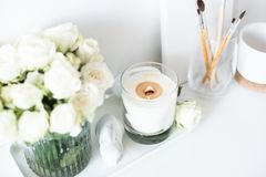 White room interior decor with burning hand-made candle and bouq. Uet of fresh roses on table, luxury home decorations in daylight closeup Stock Images