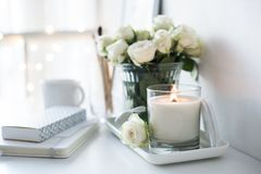 White room interior decor with burning hand-made candle and bouq. Uet of fresh roses on table, luxury home decorations in daylight closeup Stock Photo