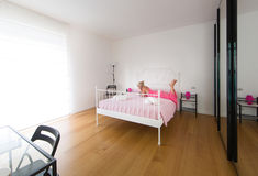 White room interior, pink dressed blonde woman on bed Stock Image