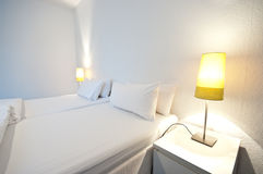 White Room with Lamps. Totally white room with white walls, bed, table and 2 lamps royalty free stock images