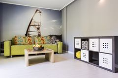 White room with photo wallpaper with windsurfing. Green sofa and coffee table stock photo