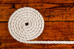 White Rope Coiled on Textured Wood Stock Images