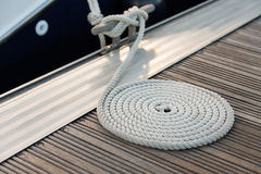 White rope coiled on a wooden dock Royalty Free Stock Photography