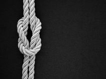 White rope tie a knot on the black Stock Photo