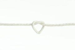 white rope tied in heart shape love knot isolated  Stock Photos