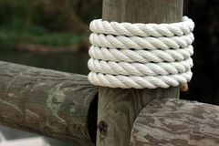 White rope wrapped around dock pier post Royalty Free Stock Photos