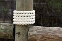 White rope wrapped around dock pier post Stock Photo