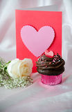 White rose, blank  Valentine with chocolate frosted cupcake. A white rose, valentine and a chocolate frosted cupcake withe candy hearts is ready for your Royalty Free Stock Images
