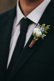 White rose and blue flowers boutonniere on groom's  black suit w. Ith tie Royalty Free Stock Image