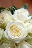 White Rose Bouquet. Bouquet of white wedding roses in a close-up shot. Petals are opened and greenery is blurred in background Stock Photography