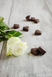 White rose and chocolate hearts Royalty Free Stock Image
