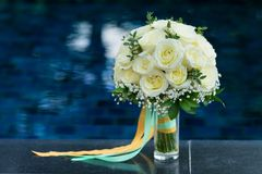 White rose flower bouquet in bundle shape for bridal in wedding. Ceremony put beside swimming pool Stock Photo