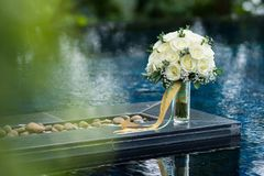 White rose flower bouquet in bundle shape for bridal in wedding. Ceremony put beside swimming pool and reflexion Stock Images