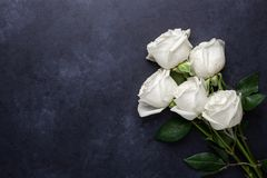 White rose flowers bouquet on black stone background. Valentine`s day greeting card Copy space Flat lay stock photography