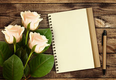 White rose flowers with notebook and pen Stock Photo
