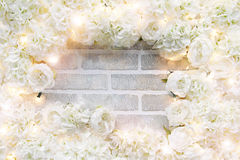 White rose frame. A frame of white roses and sparkling lights on a brick wall with copyspace in the center Royalty Free Stock Photo