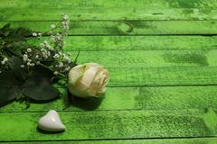 White rose and a white heart on green boards royalty free stock image