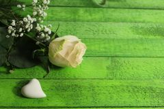 White rose and a white heart on green boards stock photo