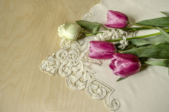 White rose and hyacinth with purple tulips on embroidered tablecloth Stock Photo