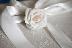 White rose and ribbon on a elegant gift box. White rose and ribbon on a elegant wedding gift box Royalty Free Stock Image