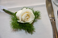 White rose at table setting. A view of a pretty white rose at a table setting next to a silver knife Royalty Free Stock Photography