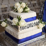 White Rose wedding cake. With blue ribbons on silver plate Royalty Free Stock Photos