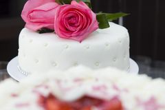 White Rose Wedding Cake. White Wedding Cake with pearls two roses on top. Another blurred cake on foreground Royalty Free Stock Image