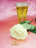 White rose and wedding rings. On satin pink background Stock Image