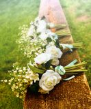 White roses on a bench before a country wedding Royalty Free Stock Photos